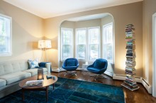 The Rug is constructed from small reclaimed pieces that were stitched together and over-dyed from a vendor in Brooklyn, New York. The mid-century gem of a coffee table is an original Jens Risom. The Bo Concept chairs sitting in the room's bay window are covered in a vivid blue wool felt.